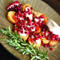 Bruschetta Topped with Apricot, Melted Brie, and Pomegranate Seeds